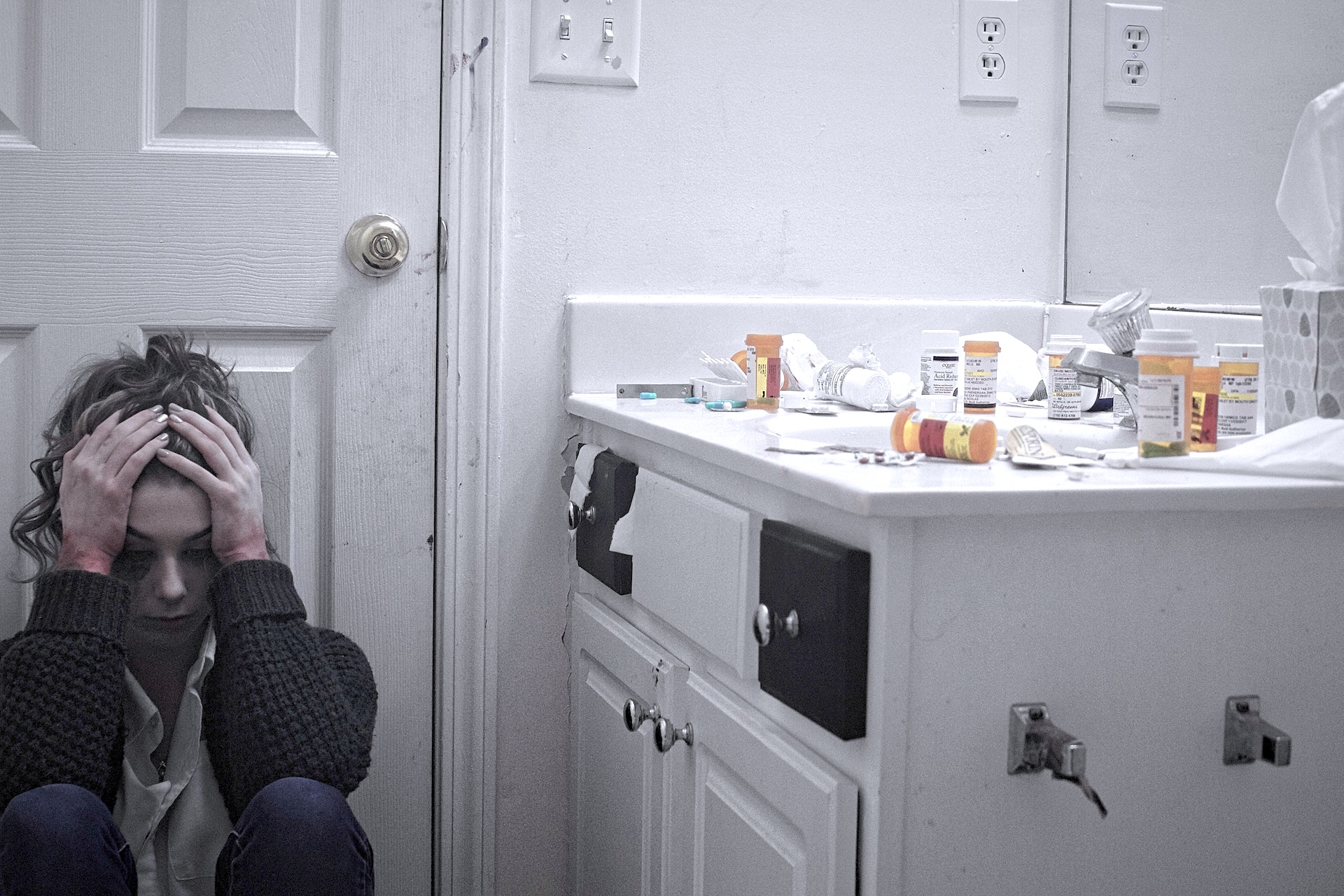 sad woman on floor with medications on the sink