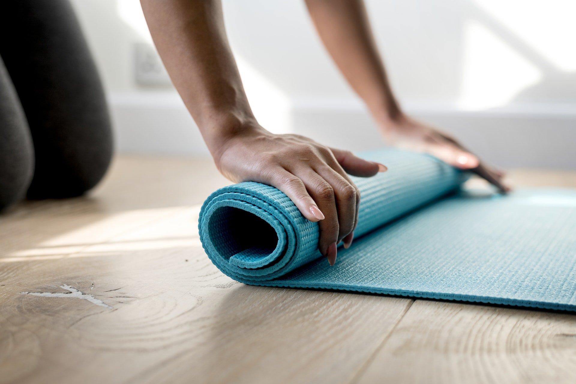 woman's hands rolling out yoga mat