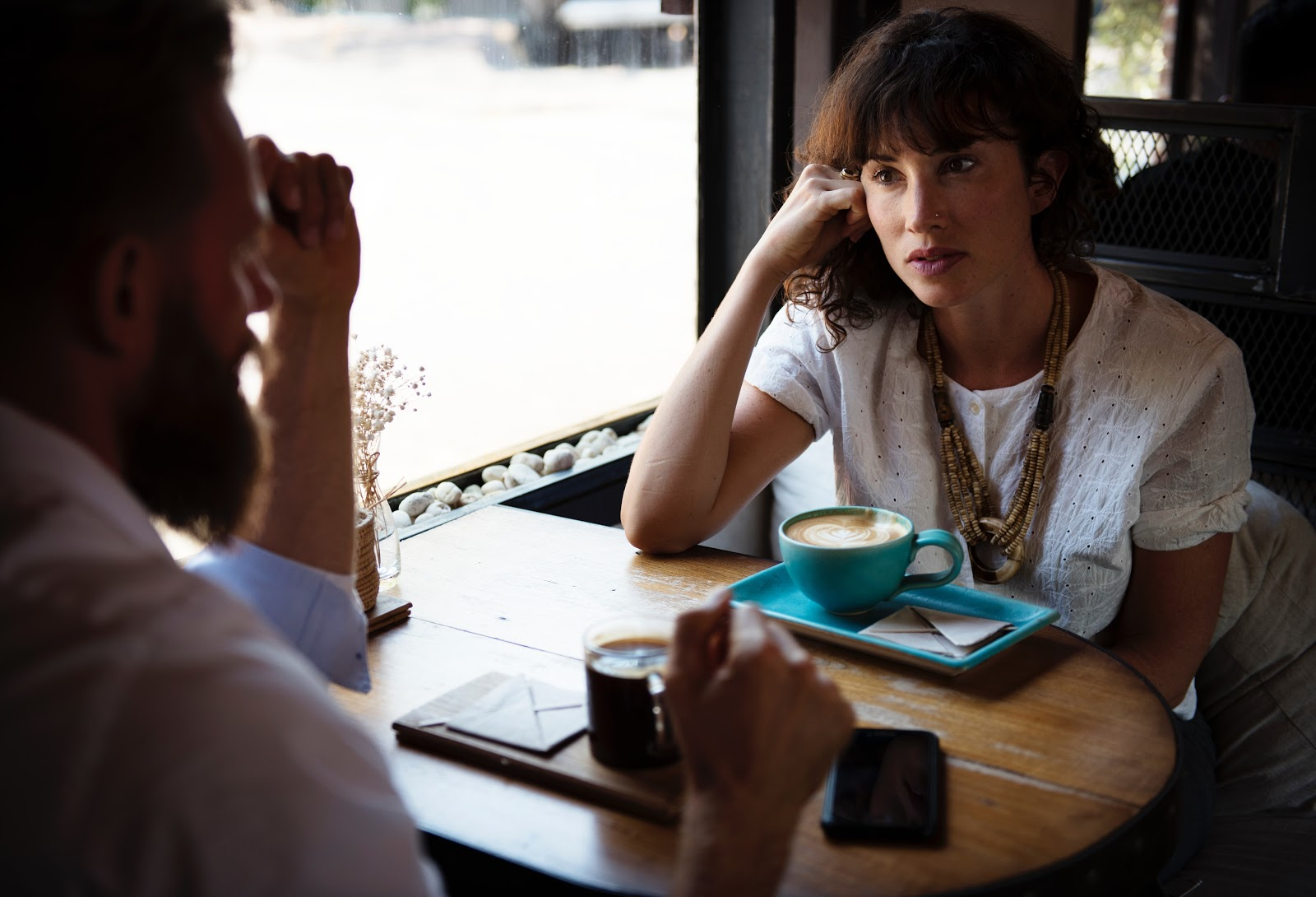 Woman listening to male while drinking coffee