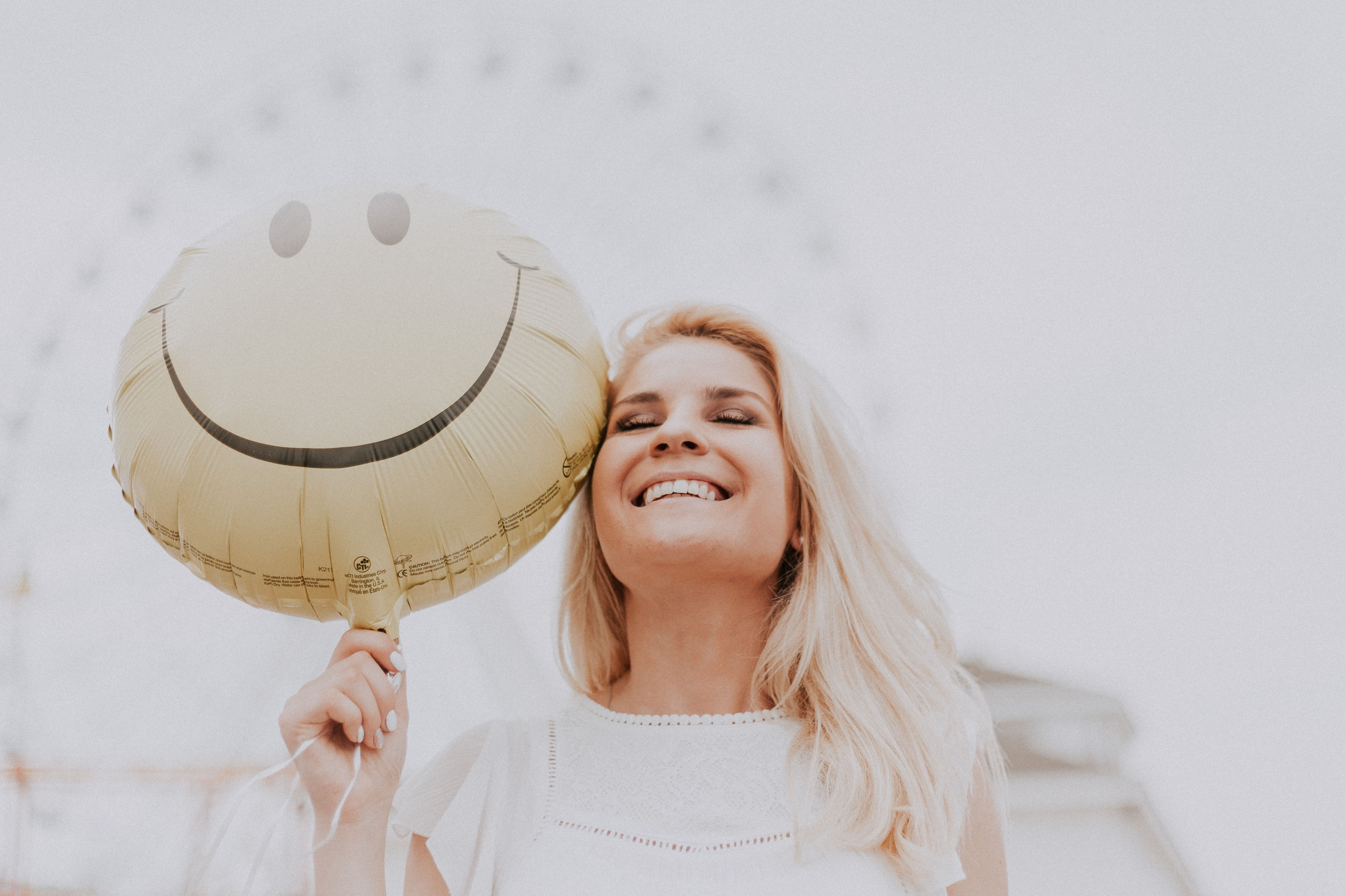 Woman smiling while holding a smiley face balloon