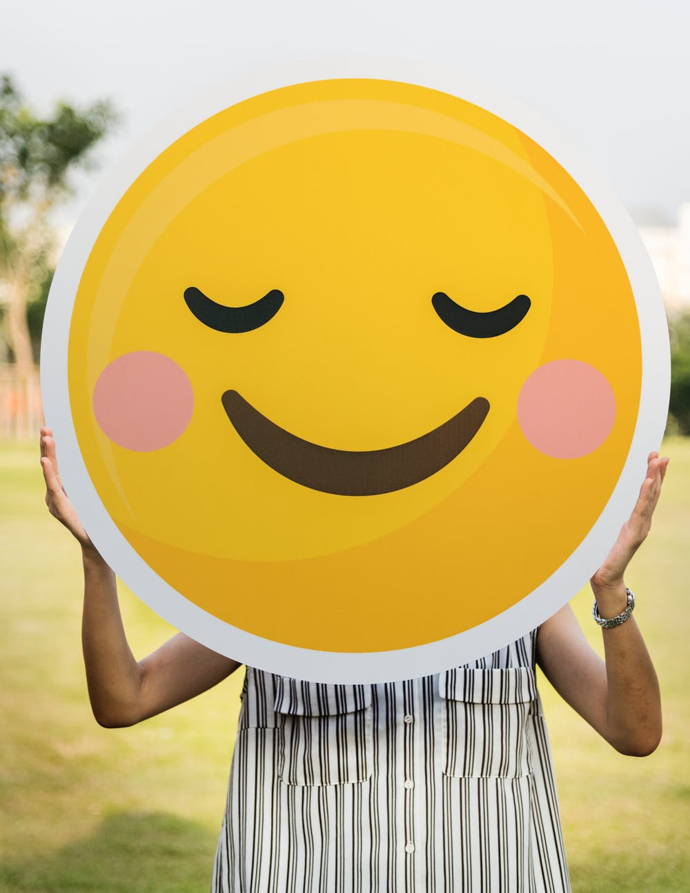 a woman, full of joy after switching to a minimalist lifestyle, holds a smiling emoticon in front of her face