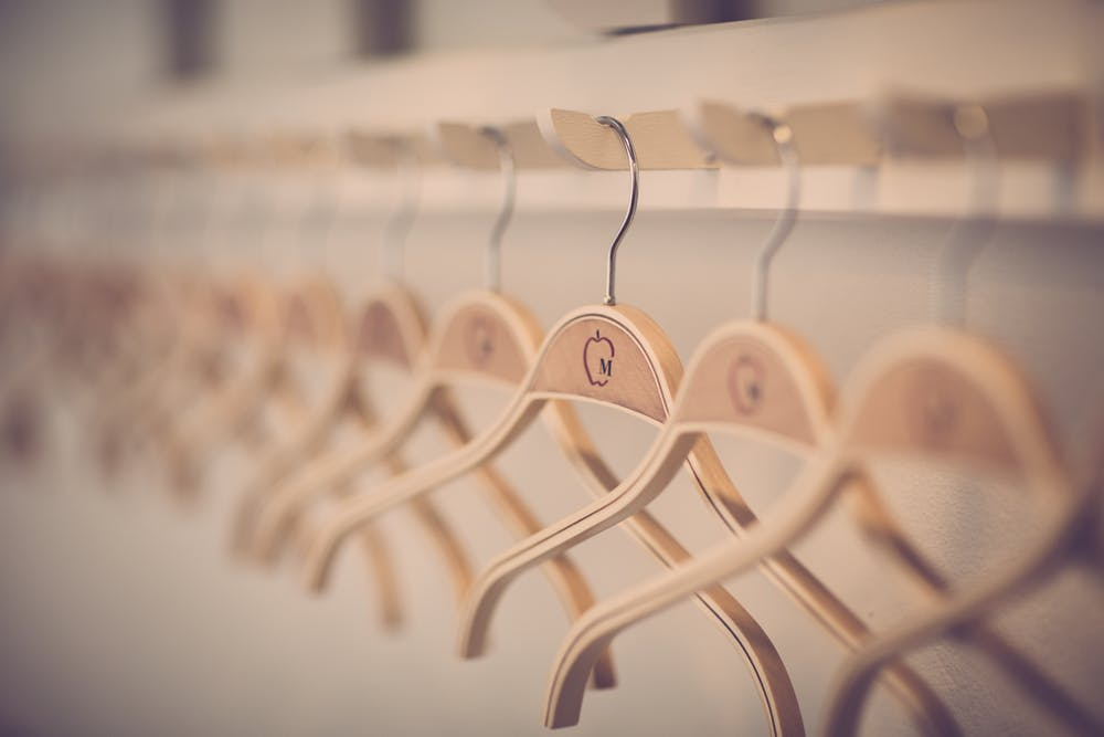 decluttered wooden hangers in a tidy minimalist closet