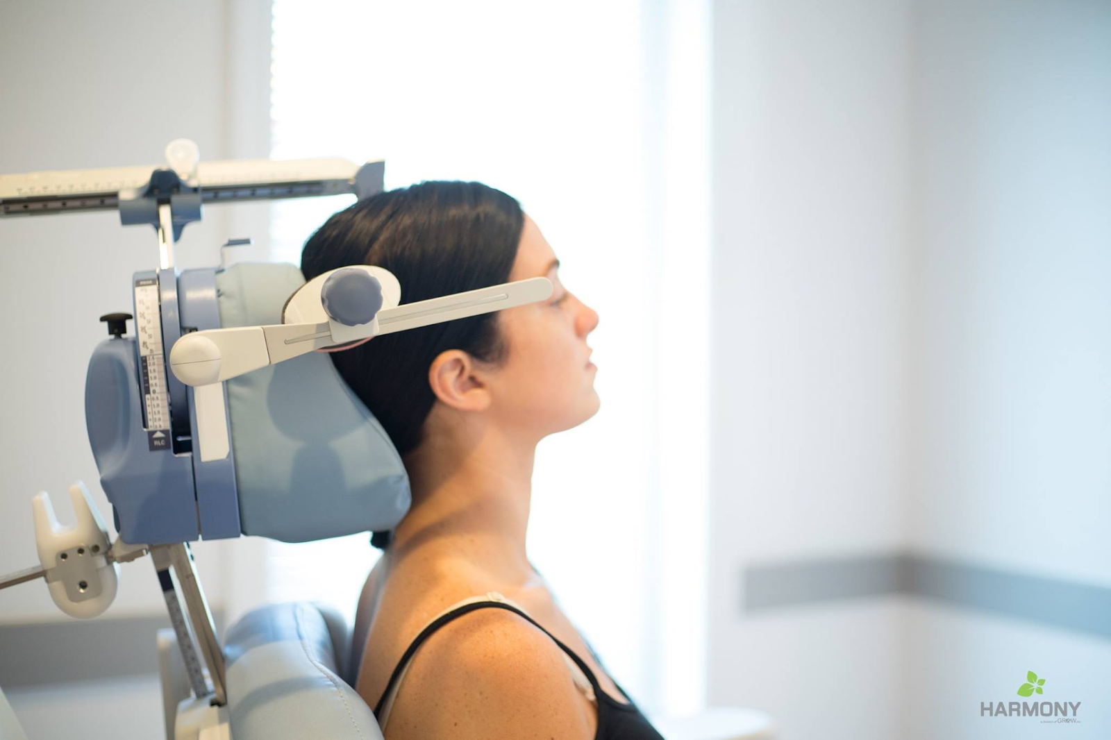 A woman sits in a chair to receive a TMS treatment