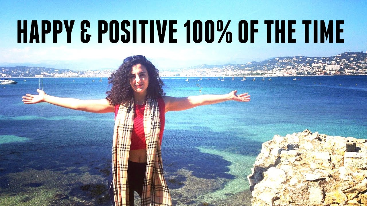 "A woman is standing in front of a body of water with her arms open, and above her is the text ""Happy & positive 100% of the time"""