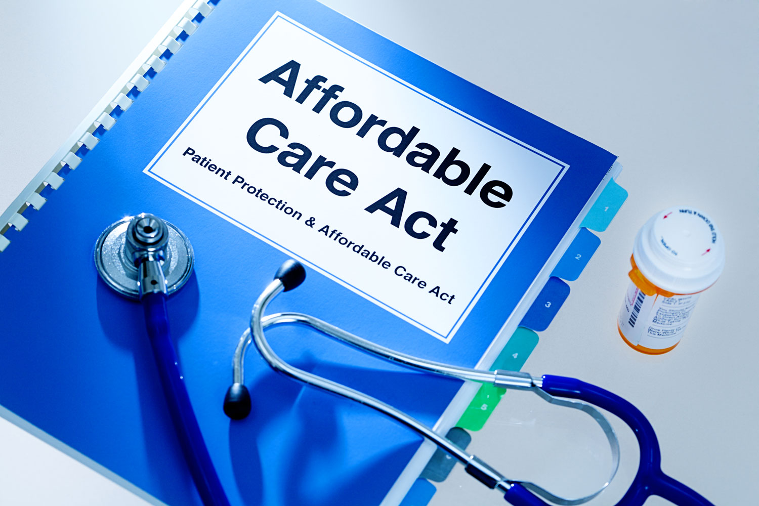 "Blue book that says ""Affordable Care Act"" with a stethoscope and pill bottle"