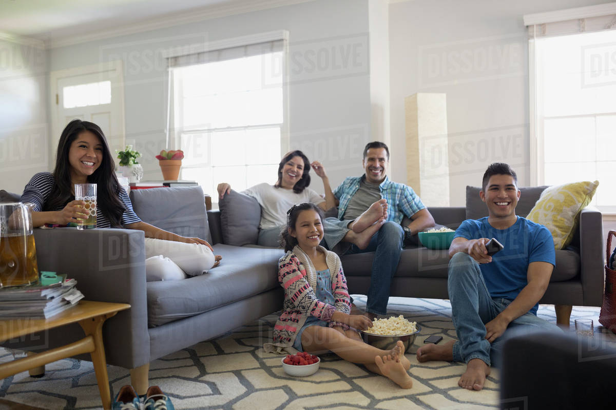 A family sitting in the living room and happily watching a movie together