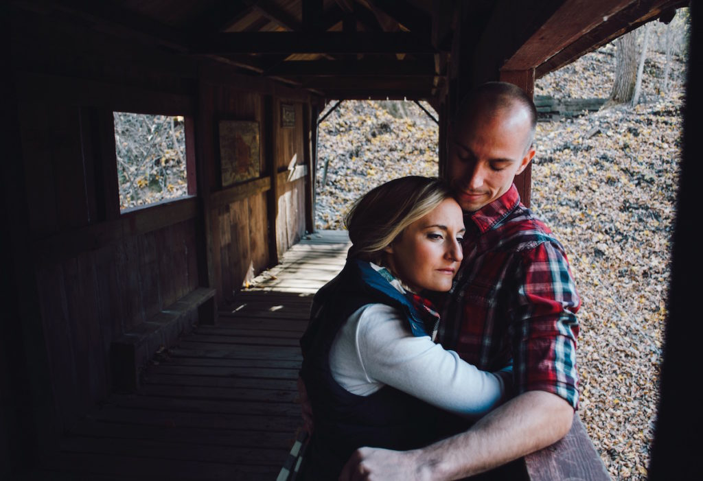 Two people on the porch of a cabin in the woods hugging