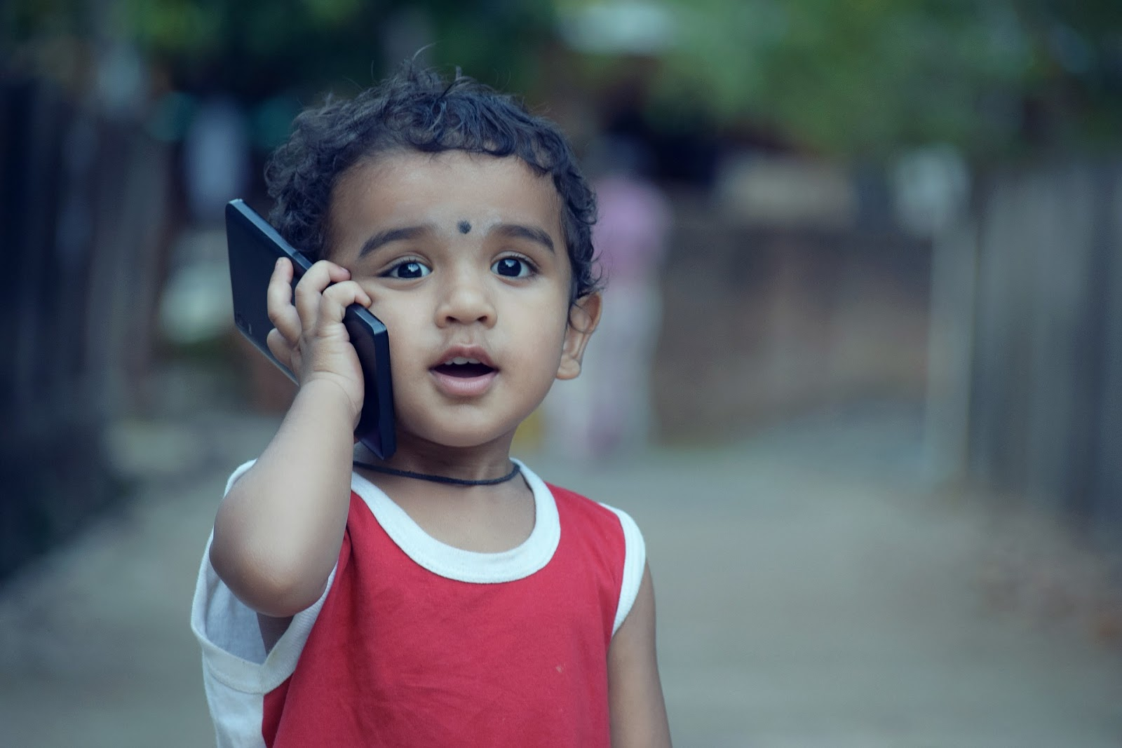 A child (2-4 years) holding a cell phone.