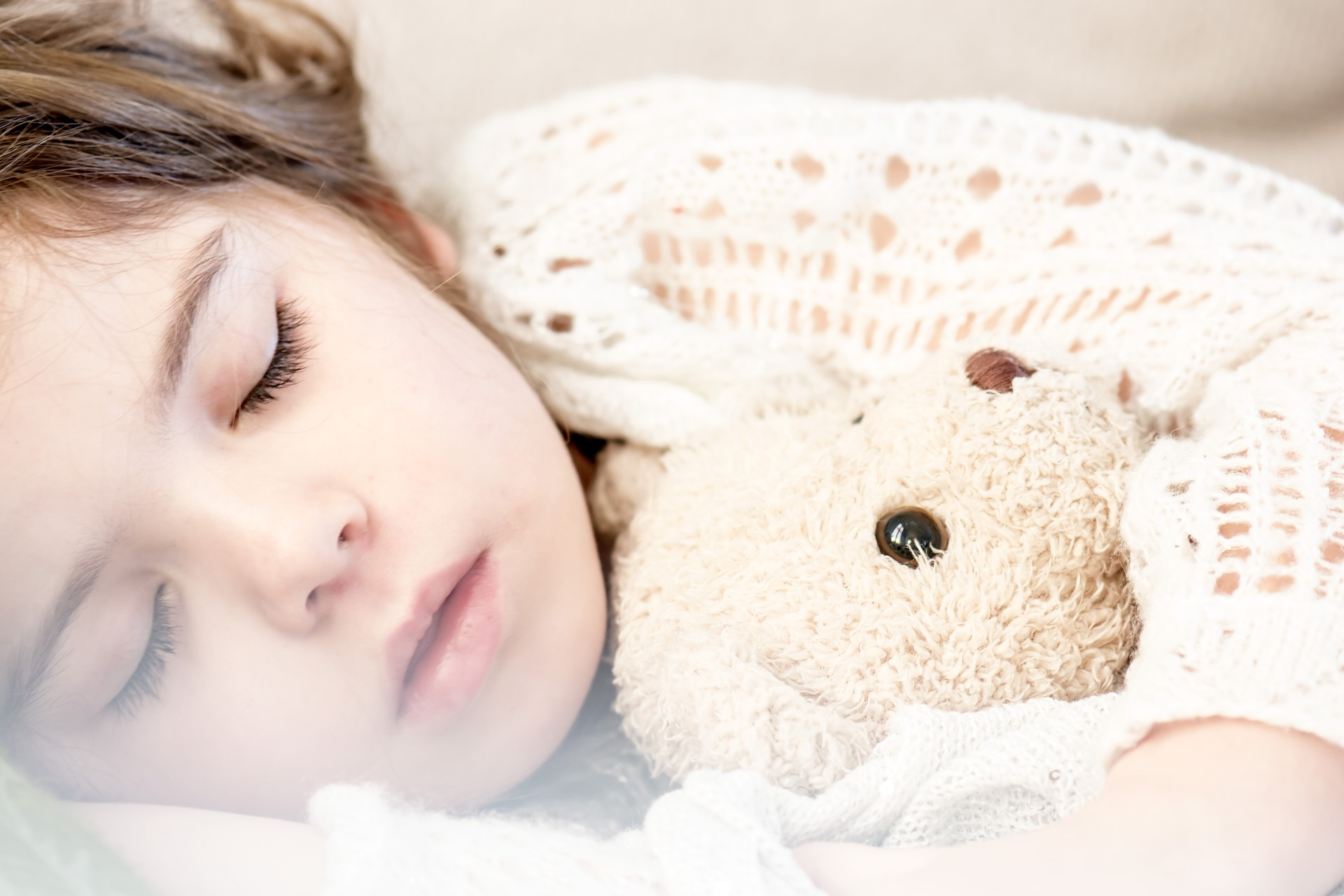 A child holding a teddy bear and sleeping.