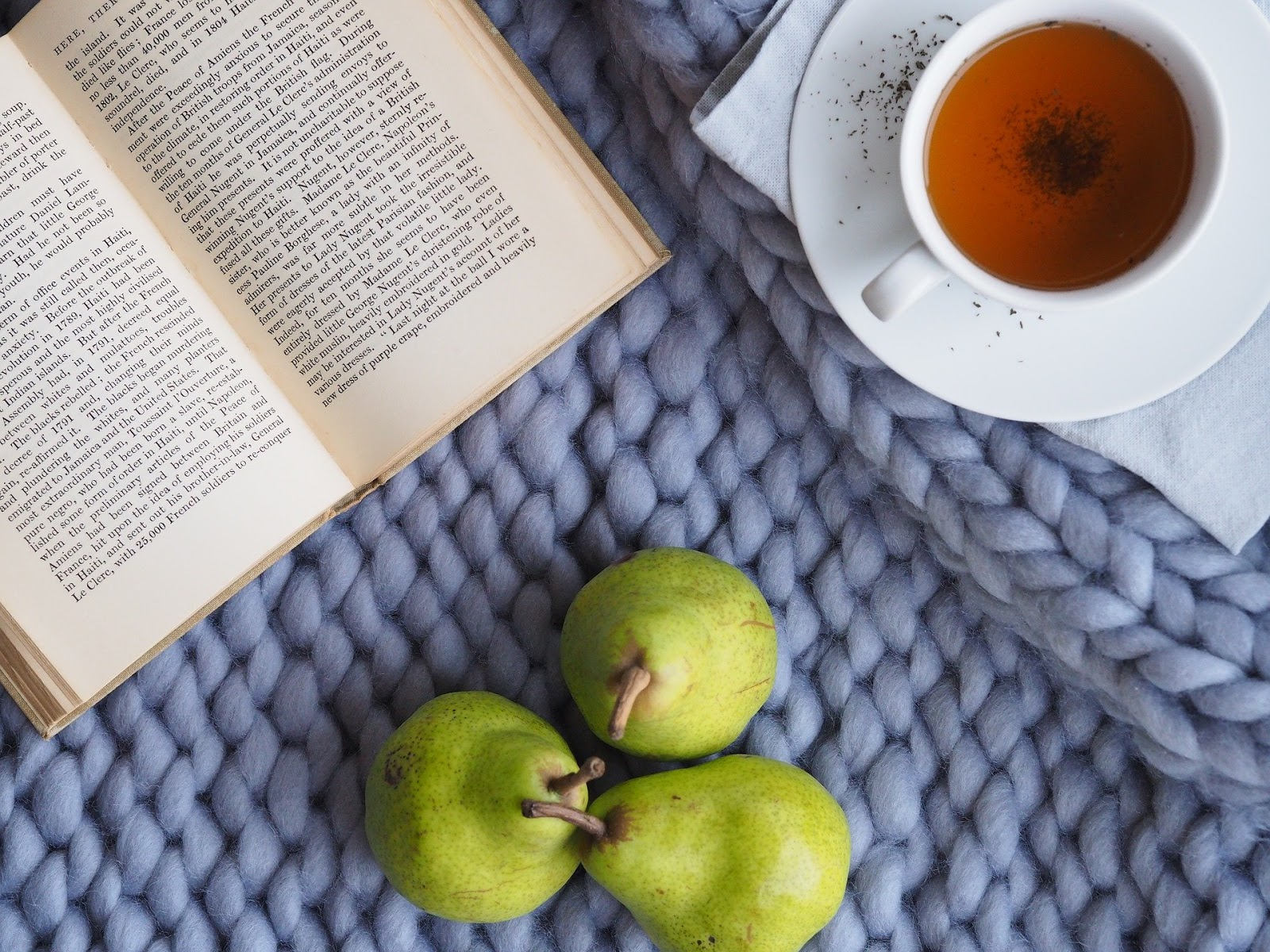 A book, a cup of tea on a saucer, and three pears on a purple woven blanket