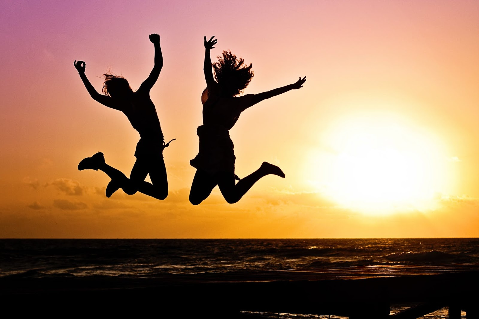 Two people are jumping in the air on a beach as the sun sets behind them.