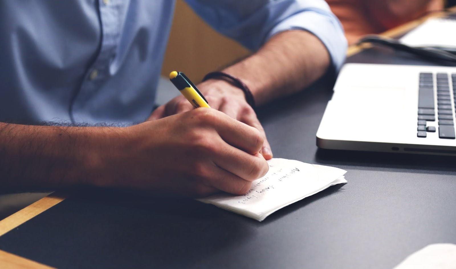 A man sits at his desk with a pen in his hand to write a list.