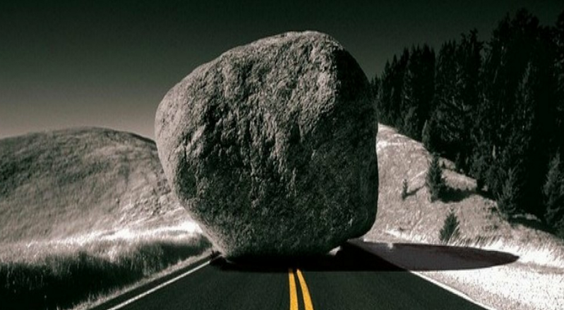 A boulder sits on a road, blocking the path towards your bad habit.