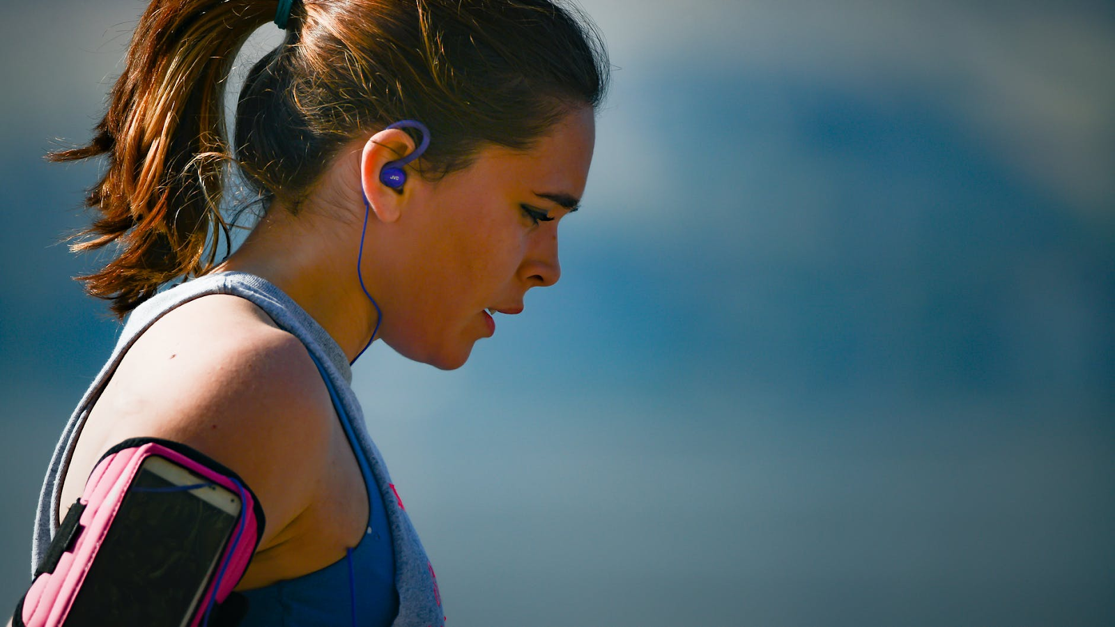 A woman is jogging while wearing a pair of earbuds and an armband that holds her smartphone
