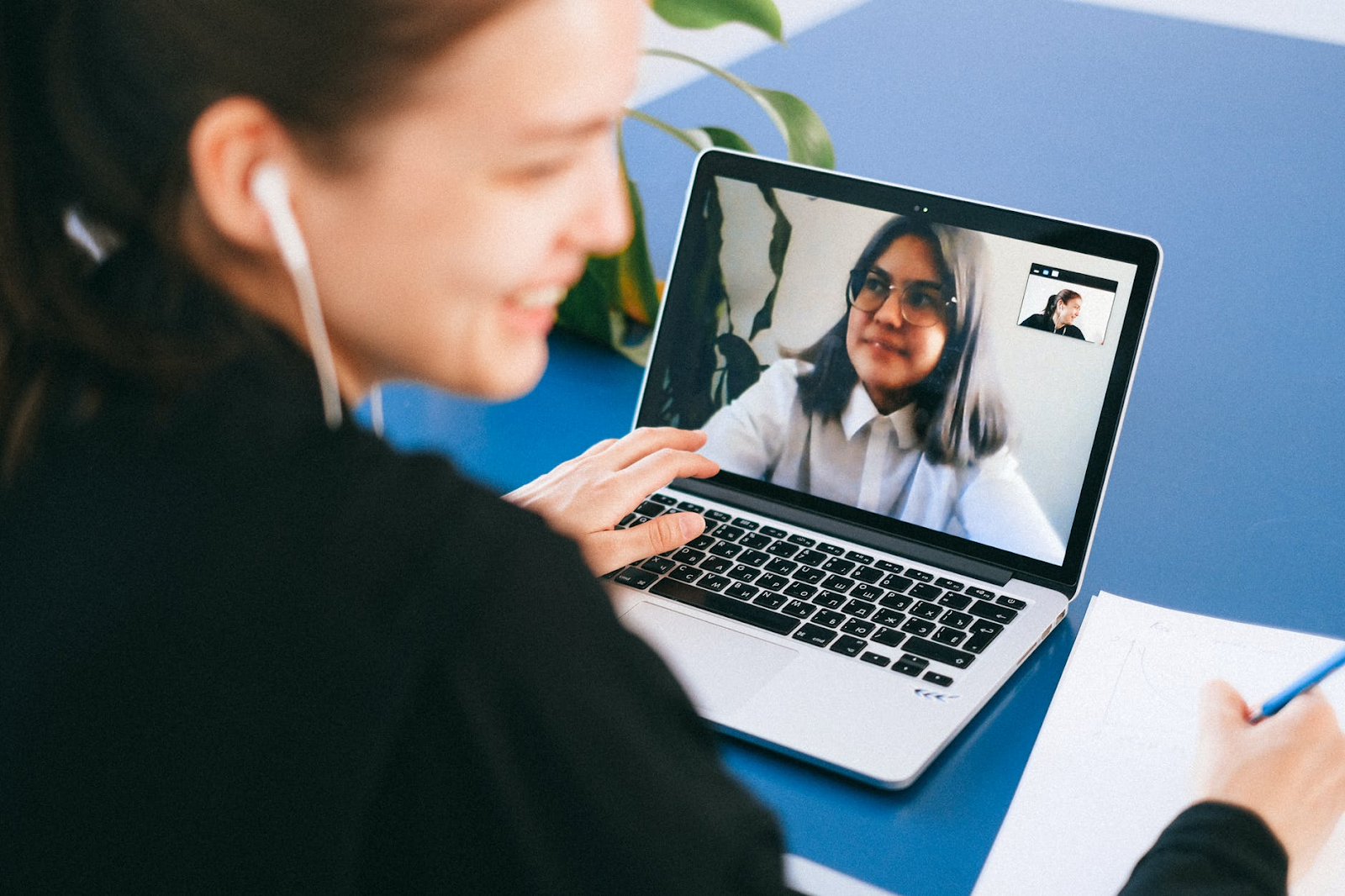 A woman chats and laughs with her friend through a video call on her laptop