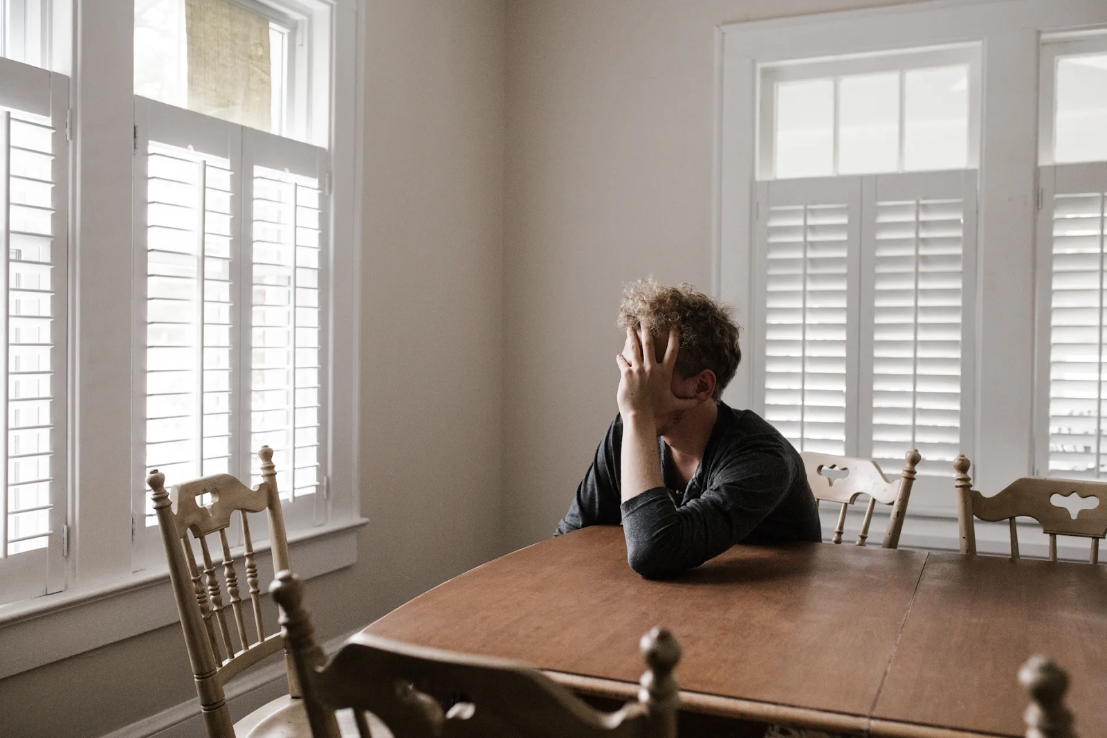 A man tiredly clutches his head in his hand as he leans across a dining room table