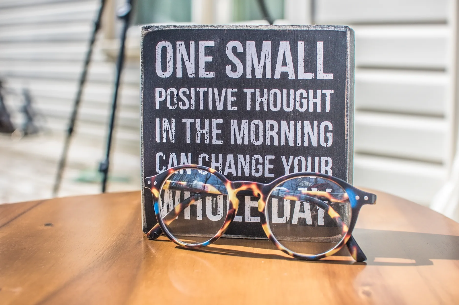 "A sign standing on a table has the words ""One Small Positive Thought in the Morning Can Change Your Whole Day."" A pair of glasses rests in front of it"