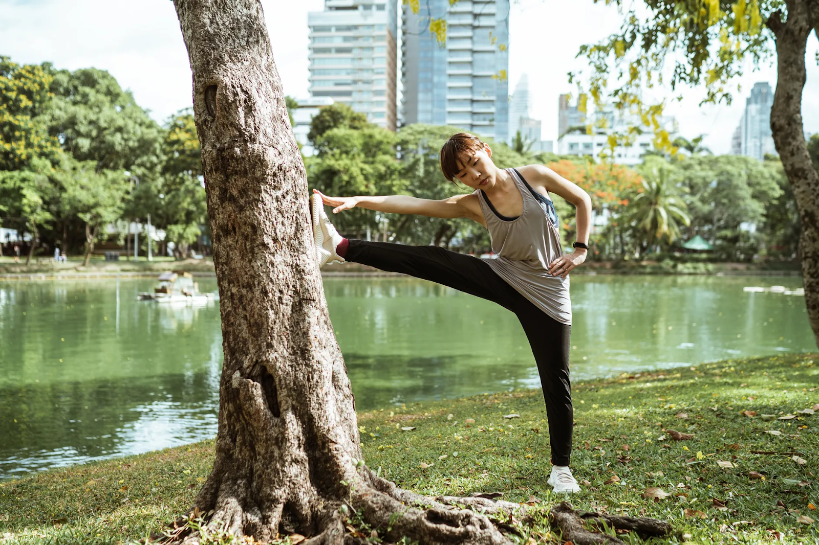 A young Asian woman stretches in front of a lake by lifting her leg against a tree