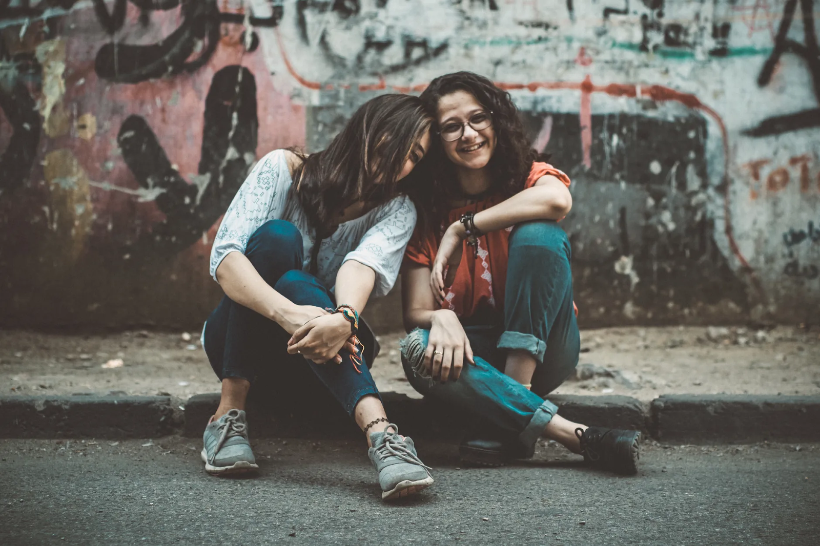 Two woman sit on a curb together in front of a graffiti-covered wall, leaning on each other and laughing