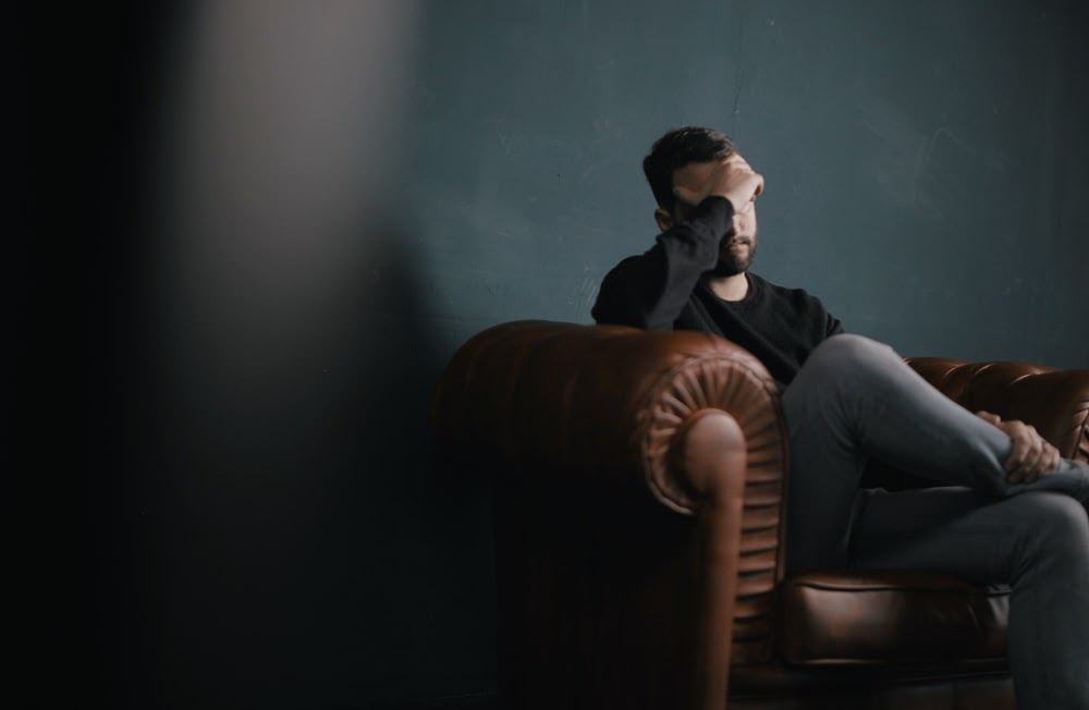 a man holds his head while sitting on a sofa photo – Free People ...