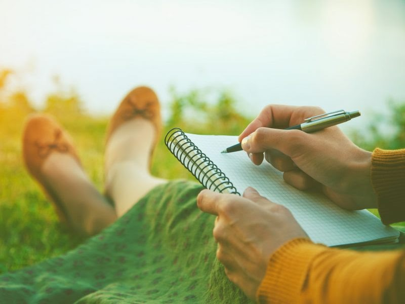 A woman sitting in grass penning something in her journal.