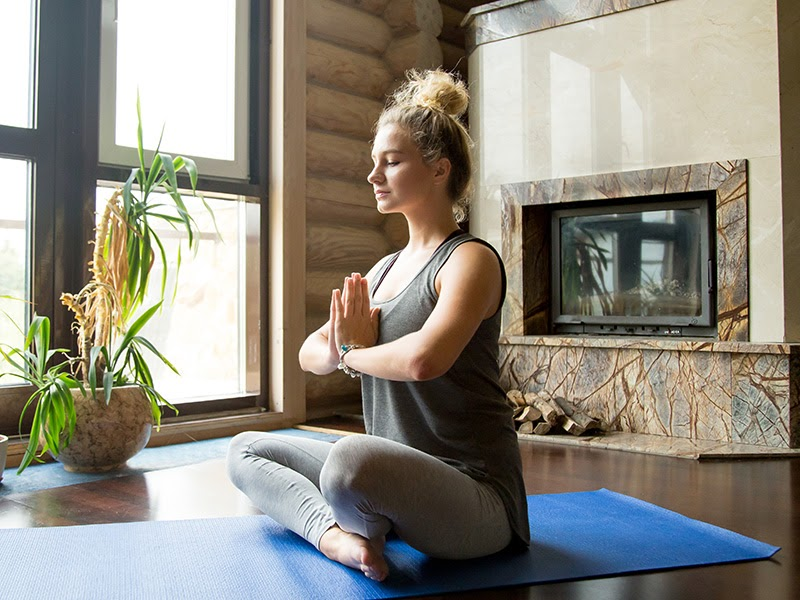 A woman meditates in a serene room.