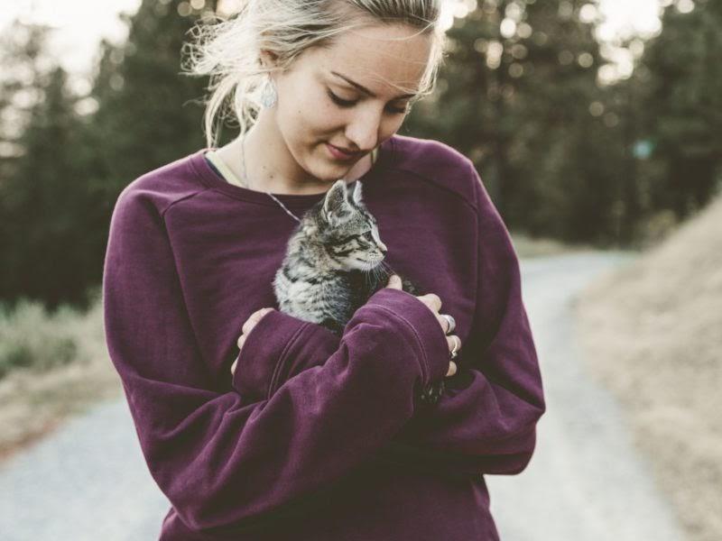 A woman cuddling a kitten.