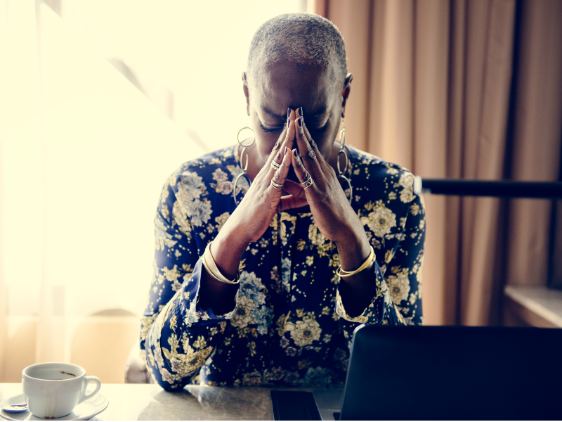 An older woman sits with her face in her hands, looking visibly stressed.