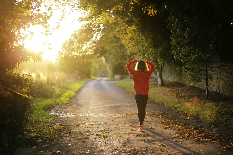 An image of a person walking down a dirt path framed with trees on a sunny day, their hands on their head.