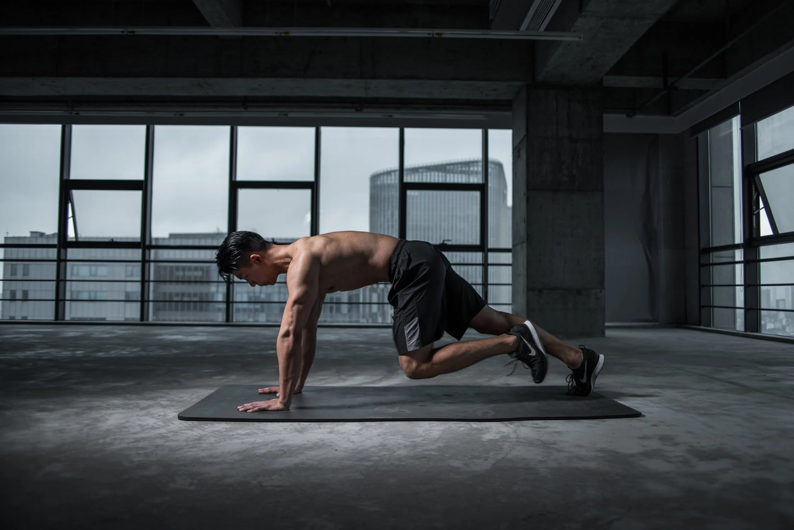 An image of a man in push-up position on a yoga mat in an otherwise empty room.