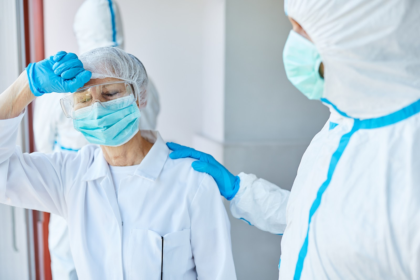 Two healthcare workers in PPE consoling each other.