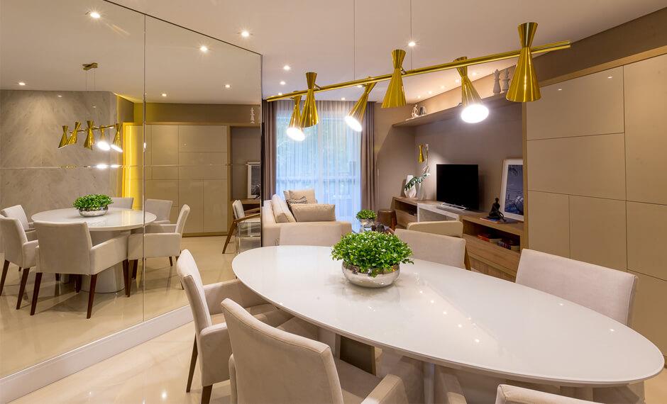 Perspectiva da sala de jantar decorada, com passagem para sala de estar, do residencial Monselle, no Centro Cívico, próximo ao Museu do Olho e Bosque do Papa, em Curitiba, Paraná