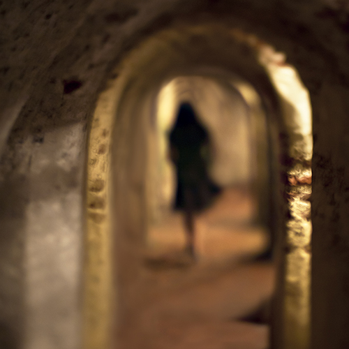 A silhouetted woman in a flowing dress walking down a tunnel in Castillo San Felipe de Barajas in Cartegena, Colombia.