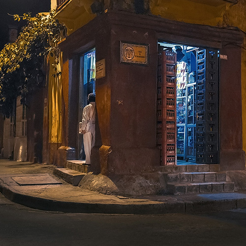 Travel photography of a man standing in a doorway of a corner store at night in Cartagena, Colombia.
