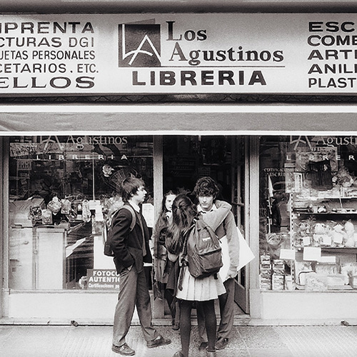 A black and white photo of 5 school children standing outside a bookstore in Buenos Aires. A girl is hugging a boy that is looking straight at the camera.