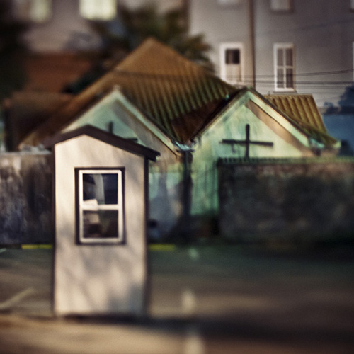 Night photography of a empty parking attendant booth in front of a church with a cross in Charleston,South Carolina.