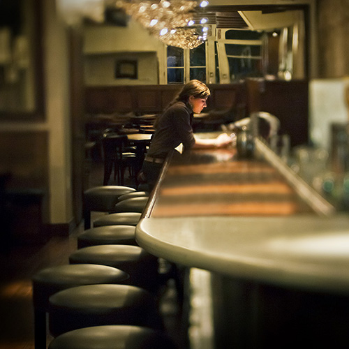 Night photography of a girl sitting along at the bar of an empty restaurant, text on her phone, in Charleston, South Carolina.
