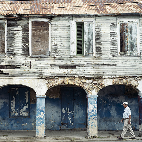 A man in a white baseball cap walking passed a very weathered wood building with a tin roof in Frederiksted, St. Croix