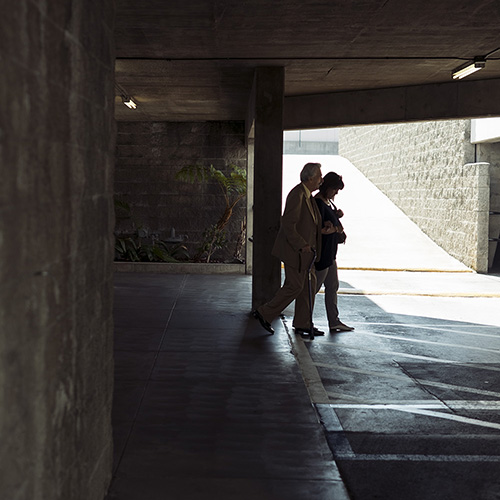 An older man and woman walking arm-in-arm out through a parking lot in Glendale, California. Significant detail on the wall for a dark photo and the couple are silhouetted from the light coming through the garage ramp.