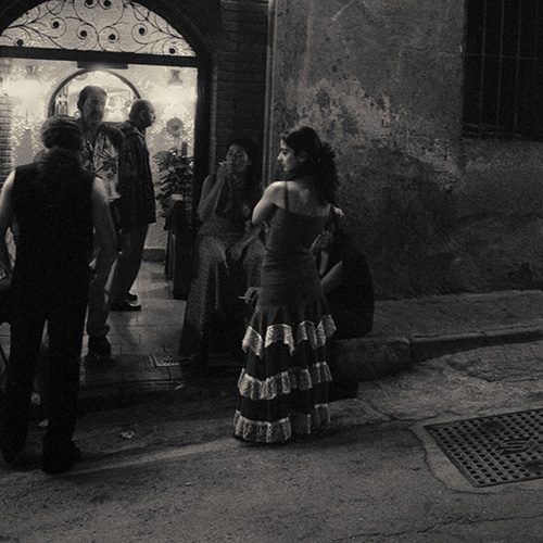 Young flamenco dancers sitting and talking outside a club in Granada, Spain.