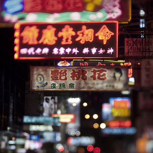 A sky filled with bright, neon street signs written in Chinese in Kowloon in Hong Kong at night.