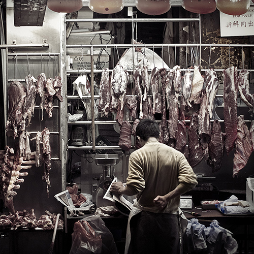 Night photography of a man reading a newspaper at an open-air meat night market in Hong Kong, China.