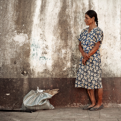 An older Mexican woman with very strong legs, standing near a wall with bag and walking stick after collecting coffee beans in the mountains in Huatulco, Mexico.