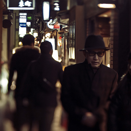 Night photography of a creepy man in a trench coat and hat walking down a busy city street at night in Pontocho in Kyoto, Japan