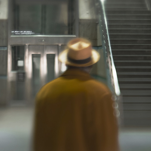 A mysterious man in a mustard yellow overcoat and hat walking to the stairs in Union Station in Los Angeles, California