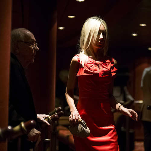 A pretty, blond woman in a red evening dress walking up stairs with an older man after a show on a cruise ship.