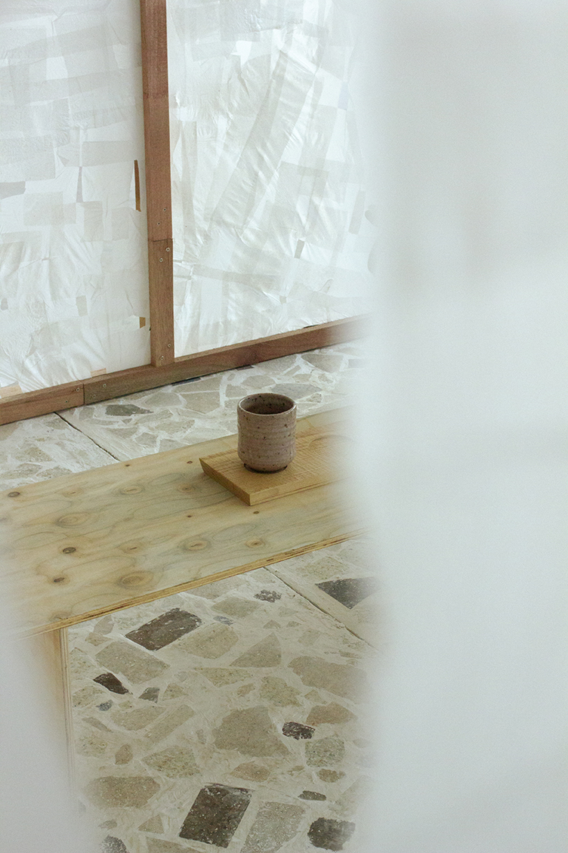 A view through a gap in the plastic screen, at a ceramic cup on the table
