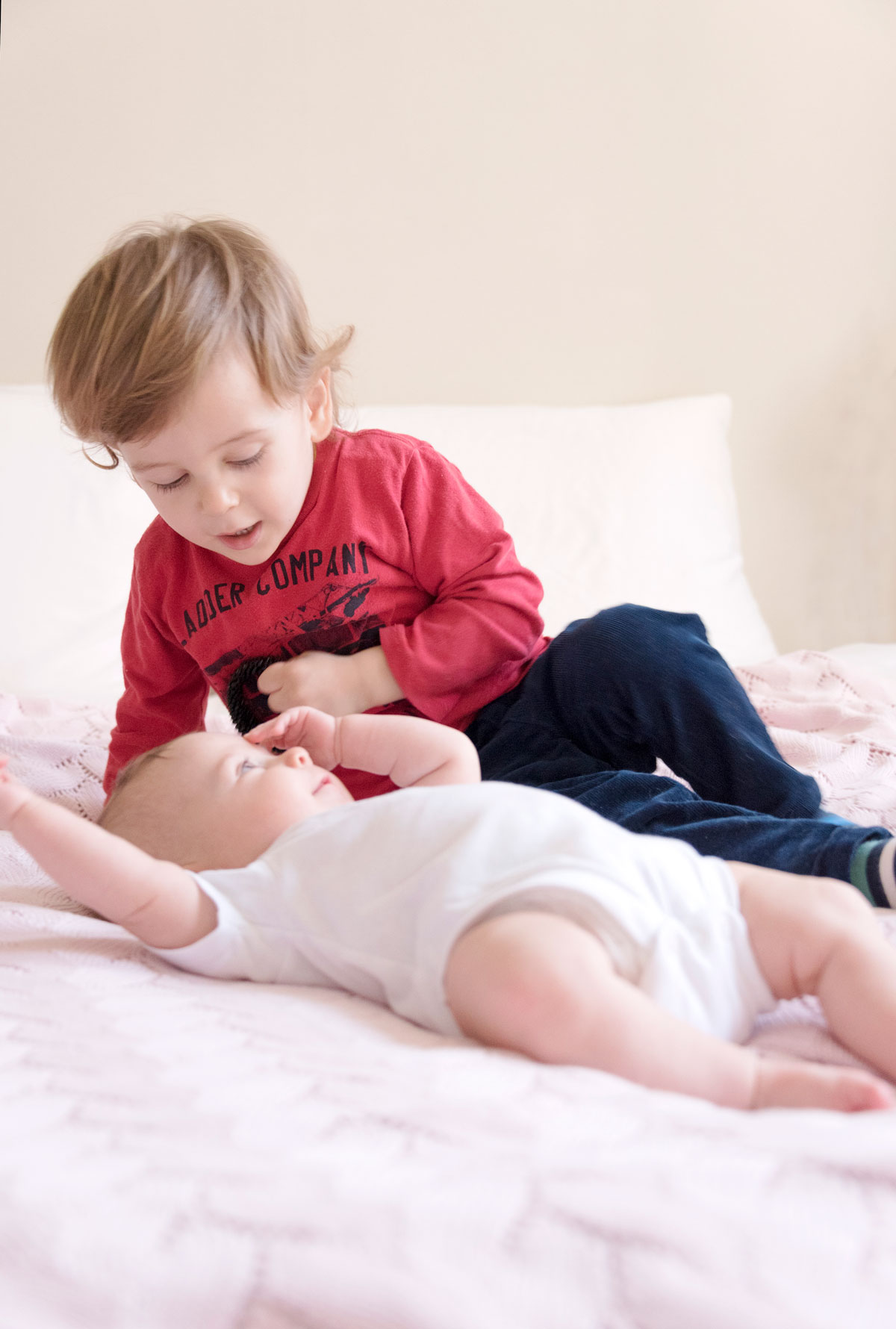 Newborn baby girl playing on a pink blanket with her brother