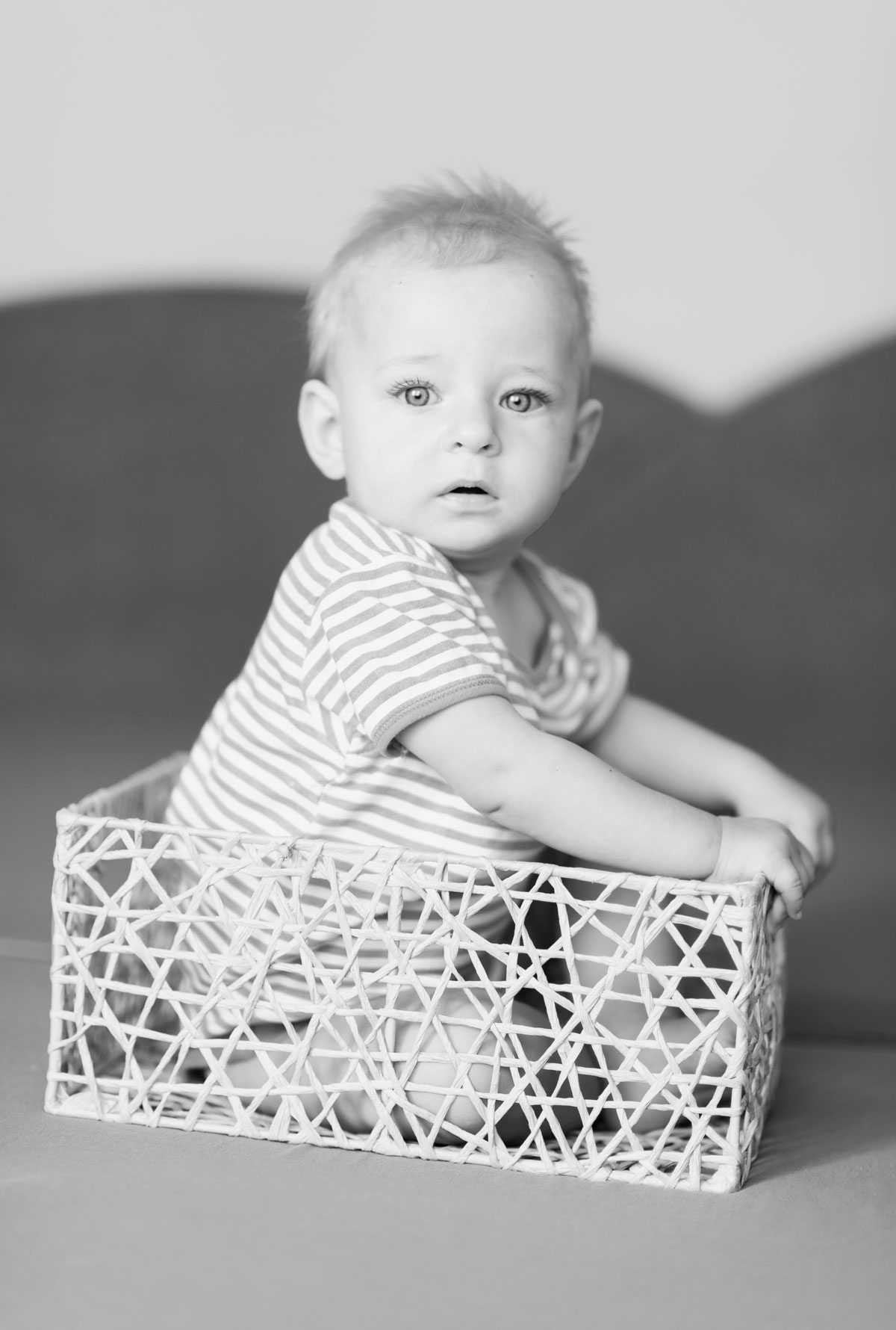 Portrait of baby girl sitting in the basket in black and white