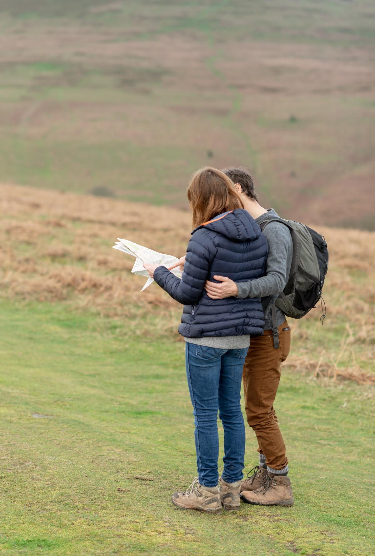 Engaged couple checking map while hiking in Wales UK